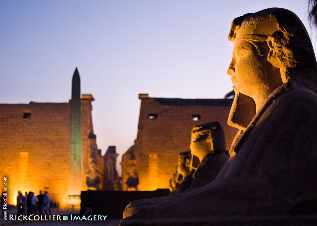 Luxor Temple stands in the background, framed by a sphinx as both are illuminated when the lights come on at sunset in Luxor, Egypt.