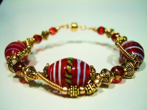 Color of Red is always a bold way of expressing one's self. This Bracelet was created using Red lampwork Glass Beads with White Swirls wire-wrapped with Gold Plated artistic beading wires and accented with Golden metallic seed beads , Red & Gold color cathedral glass beads with Antique Gold plated metal spacers and Magnetic Clasp. Measures about 7 inches ~ Price = US$25.75 (S35)