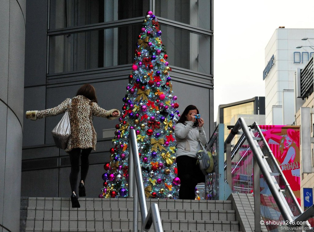 Great colors for a xmas tree here at the top of the stairs for 109 store. The girl on the left seems pleased to see the tree as well.