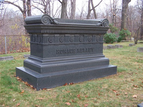 Dark gray rectangular tomb with name Horace Kelley in capital letters, above that a pattern of carved Tudor roses, topped by a carved cushion with the edges curled under