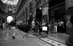on Gucci! (Rickseventy79) Tags: street white black milano lies bessa streetphotography hp5 lombardia ilford bessal galleria voigtlnder emanuele vittorio telltale  guccy 21mmcolorskopar rick79 riccardomelillo