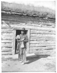 Indian Man Standing in a Doorway (The U.S. National Archives) Tags: roof house man hat wall montana indian nativeamerican logcabin blanket sodroof flatheadreservation usnationalarchives flatheadirrigationproject nara:arcid=4492623