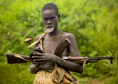 Mursi woman and Kalashnikov Ethiopia (Eric Lafforgue) Tags: portrait people woman girl face war dam cu