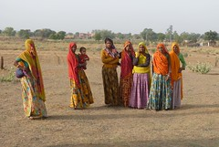 villagers67 (Johnnie Utah) Tags: orange baby fashion yellow women colorful village desert farmers gorgeous group posed farmland dirt local arid skirts rajasthan interaction saris