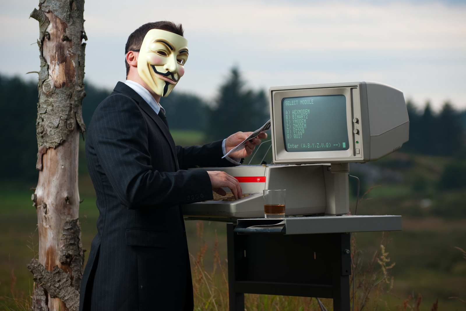 "A man wearing a suit and an ""Anonymous"" Guy-Fawkes mask, using an old-fashioned green-screen text computer."