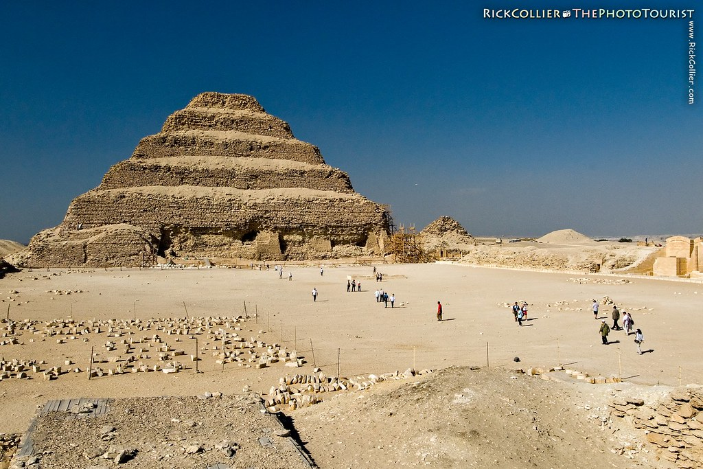 Tourists wander the arena courtyard in front of the famous step pyramid of Djoser at Saqqara, Egypt.