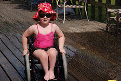 Summertime Anastasia (Light Saver) Tags: anastasia waterplay summer swimsuit pink red hat sunglasses wheelchair playing fun sun water sprinkler disability rainbow gettyproposed122009 specialneeds spinabifida blueribbonwinner allmyimagesarecopyrighted donotusewithoutwrittenpermissions ignoranceofcopyrightlawsisnoexcusetobreakthem donotcopy allimagesarelicensedthroughgettyimages contactmewithanyquestions