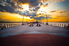 Stand Strong (13thWitness) Tags: ocean nyc newyorkcity sunset sky people orange playing ny colors yellow brooklyn clouds standing fence bench island lights pier belt sitting vibrant watching pop symmetry explore parkway tables frontpage staten bayridge nycsunset ihatetagging weliveinbrooklynbaby beltpkway