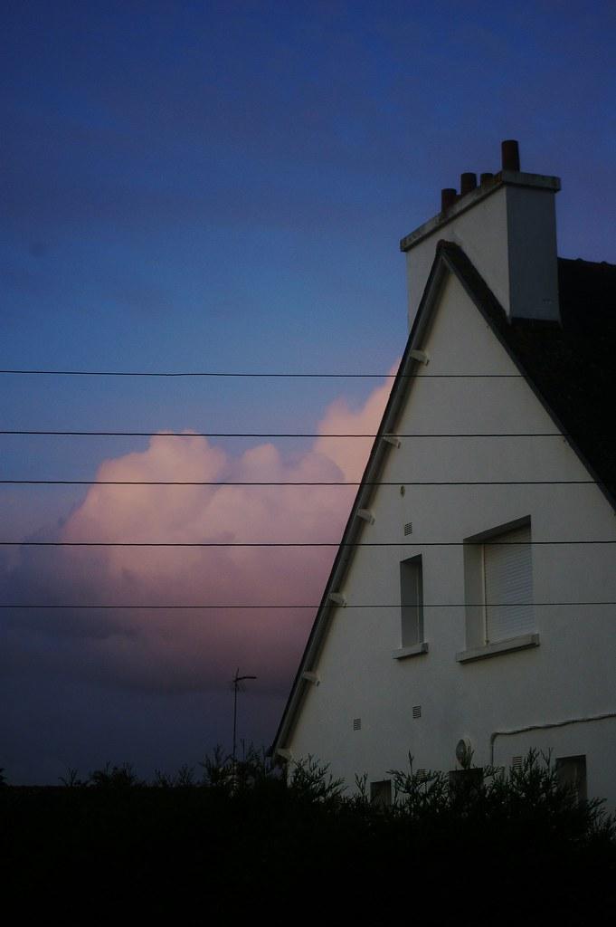 Matin breton 1 / Image illustrant l'article. Photo d'un pignon de maison bretonne, blanche, avec un ciel bleu, des nuages roses et une haie sombre en bas.