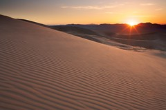Kelso Dunes (Nick Carver Photography) Tags: california sunset usa sun texture nature horizontal season landscape outdoors landscapes spring sand rocks desert time patterns country textures sunburst names southerncalifornia sanddune orientation sanddunes celestial mojavedesert regions citystate mojavenationalpreserve kelsosanddunes natureparks photospecs stockcategories ncpfineartprint geographicfeatures locationssubjects