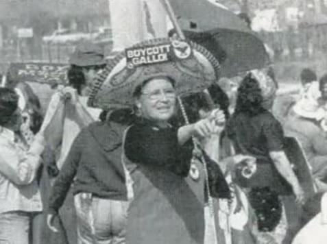 An older De La Cruz at a protest. She is pointing and wearing a sombrero that reads 'Boycott-Gallo!'