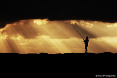 The Fisherman (-yury-) Tags: ocean sea sky sun silhouette clouds sunrise canon fisherman sydney australia 5d rays sunbeam sunray longreef supershot abigfave ultimateshot