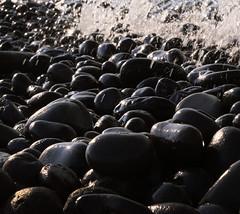 Black pebbles (Robyn Hooz) Tags: black pebbles ciottoli neri lava sole sun riflesso eolie onda wave mare sea nero lipari