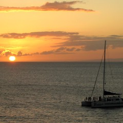 A sailboat full of patrons enjoying the sunset off of West Maui