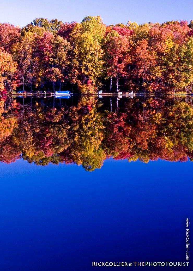 Boats are put away for the season, parked under the brightly colored foliage of fall, at Lake Thoreau in Reston, Virginia, USA.