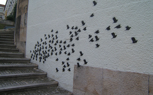 graffiti of a flock of birds in silhouette, seeming to emerge from a curved stone stairway