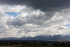 白い山並みに雨雲が近づく
