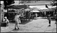 (Georgios Karamanis) Tags: street people bw white playing black boys water caf girl hat children chairs wide greece guns umbrellas serres karamanis