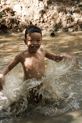 Jumping for Air (Vicariously_Me) Tags: light boy fish water smile canon jump pond joy sigma vietnam shade splash xsi 2470mm hsm travinh earthasia cauquan