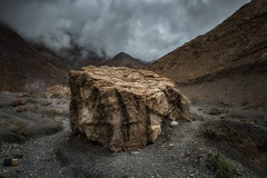 The Road to Erebor (David Colombo Photography) Tags: deathvalley nationalpark deathvalleynationalpark rock boulder canyon clouds mountains gravel brown black grey gray moody ominous desaturated landscape bigrock hugerock nikon d800 davidcolombo davidcolombophotography desert cloudy