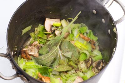 leeks, mushrooms, herbs cooking in a pot