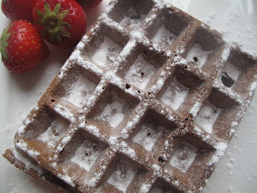 Snow covered chocolate waffles with strawberries
