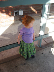 Speck in a skirt, looking into teh distance (bus_stop_lean2)