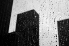 The city beyond the window (Airicsson) Tags: new york city nyc blackandwhite bw usa white ny newyork black blur building fall rain silhouette america skyscraper island lumix us drops noir bokeh manhattan moma drop falls nb panasonic midtown et blanc raindrop twop blackwhitephotos lx3