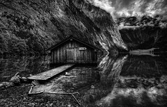 The Boathouse - 1/2 (timo.frey) Tags: trees sky bw lake mountains alps nature water clouds reflections germany landscape bayern deutschland bavaria see berchtesgaden blackwhite wasser ast natur himmel wolken berge boardwalk alm canon5d alpen ufer schwarzweiss limb landschaft bume waterside blackdiamond steg idylle obersee reflektionen knigssee holzhtte ef1740mm committeeofartists timofrey fischunkenalm