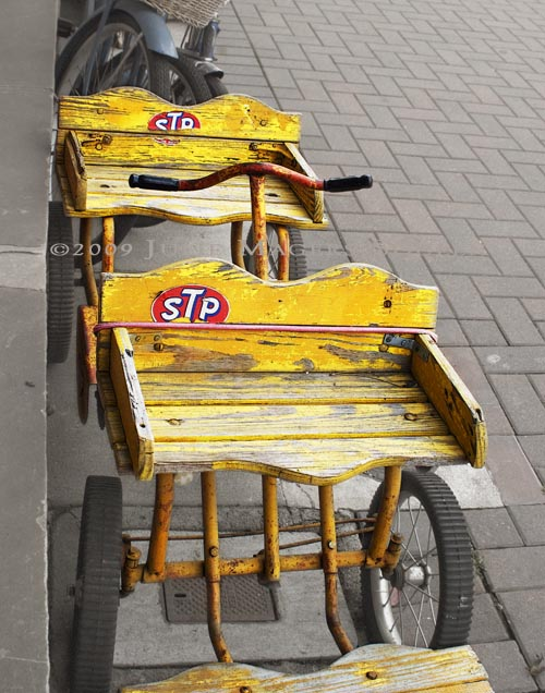 A child's bright yellow antique wagon on drab sidewalk