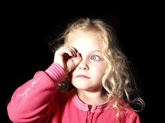Invisible telescope? (FragilePhoto) Tags: pink portrait black silly cute girl goofy kid child hand blueeyes young adorable curls olympus niece blonde pajamas watermark aryan lookingthrough footypjs flourescentlamp fragilephoto invisibletelescope