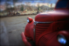 The Forgotten Fargo (justb) Tags: old red blur brick broken colors car station wall forest truck canon painting concrete hope blurry mural colorful bc parking lot headlights grill gas stained grease abandon wilderness asphalt fargo abandonment justb 40d