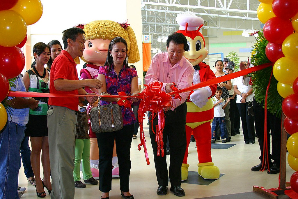 Councilor Meg Santos, representing Mayor Jun Acharon cuts the ribbon at Jollibee Robinsons with franchisees, Philip and Doming Teng. Behind them is Cherry, Domings ageless beauteous wife.