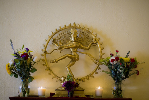 Golden statue surrounded by flowers and lit candles