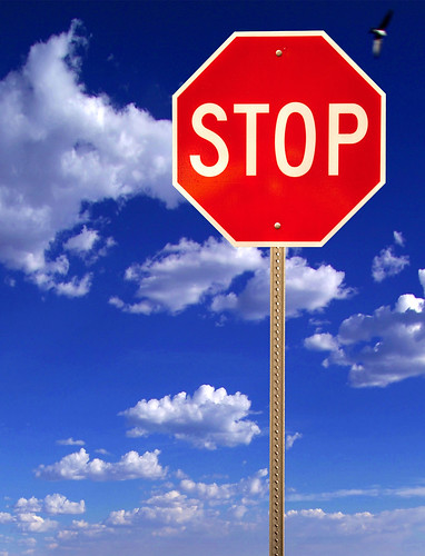 Stop sign on blue cloudy sky by emagine6.