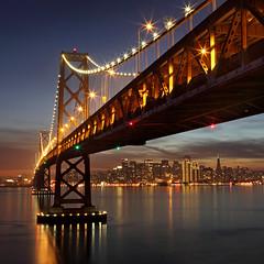Bay Bridge and SF from YB (Rob Kroenert) Tags: sanfrancisco california bridge blue sunset usa holiday skyline island lights bay twilight san francisco downtown pyramid dusk center hour baybridge embarcadero transamerica yerba transamericapyramid buena yerbabuenaisland sanfranciscobaybridge