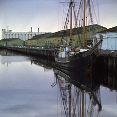 Falie and sheds (Tony Kearney) Tags: loss demolished ketch portadelaide scannedfromfilm olympusom2n falie croppedsquare maritimeheritage afewyearsback wharfsheds wharfshedsgonenow