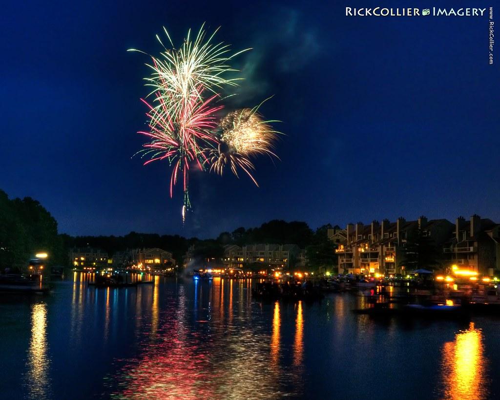 Independence Day (Fourth of July) fireworks illuminate revelers on decks and dockboats on Lake Thoreau in Reston, Virginia, USA.