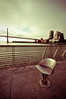 Seat With a View (Ame Otoko) Tags: sanfrancisco california city clouds dawn pier chair nikon industrial alone sad image artistic sale steel empty 14 stock rail wideangle commercial baybridge gloom lonely strength absent emptiness lonliness absence d90 justimagine builttolast