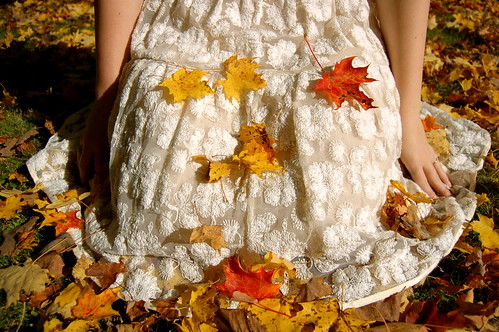 Bride kneeling in fall leaves