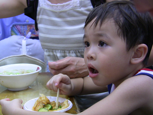 A little boy eating tempura