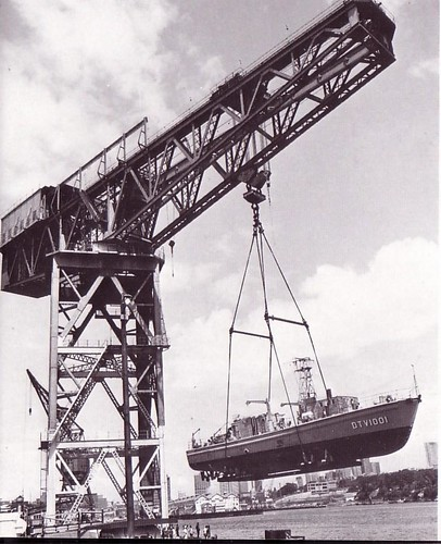 Early 1970s: Dive Tender HMAS SEAL [ex-HMS WINTRINGHAM], 120 tons,  gets a lift from Garden Island's Hammerhead crane  - Photo RAN.