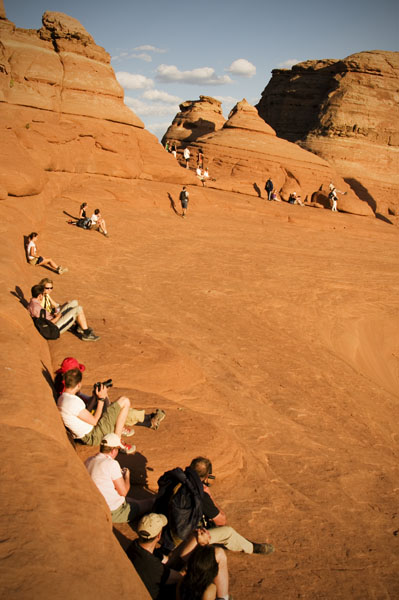 Fans of the famous golden arch (Delicate Arch) wait for sunset.
