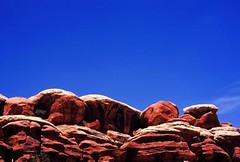 Where once was sea () Tags: sky usa texture film geotagged utah nationalpark nikon rocks fuji ishootfilm cliffs velvia canyonlands fujifilm 100 geology velvia100 f80 needles 100iso needlesdistrict elephanthill geo:lat=3814168 geo:lon=109827422