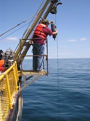 "Standing on the boat's ""hero"" platform, Jeremy retrieves a Niskin bottle filled with water. ~photo Jennifer Yauck"