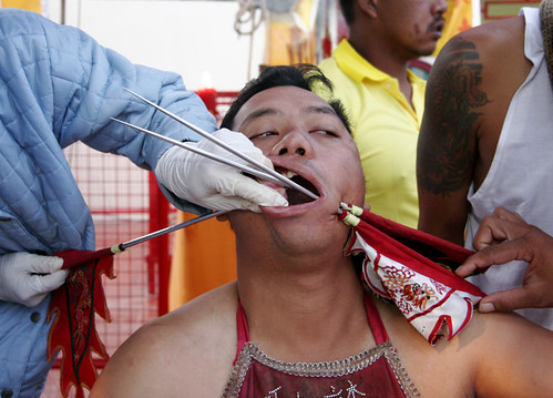 Man getting his cheek pierced at the Phuket Vegetarian festival