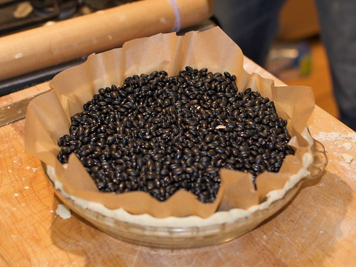 Baking a pie shell, using beans and parchment paper to weigh down the shell