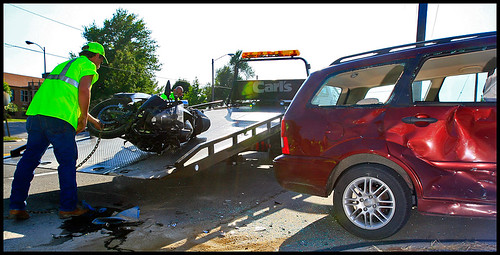 A Carls Towing & Transport worker helps clear a motorcycle from Business Loop 70 between South Providence Road and Seventh Street. The motorcyclist crashed into a red Ford Focus, shown, on Tuesday. According to eyewitnesses, Columbia resident Daniel Morris was traveling westbound on Business Loop 70 on his motorcycle when he quickly passed a truck driver and broadsided Columbia resident H.R. Ricketts. Ricketts was turning left onto a driveway.