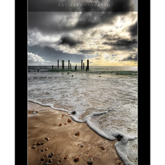 The Unforgiving Sky | Port Wilunga, South Australia :: HDR (Artie | Photography :: I'm a lazy boy :)) Tags: hdr portwilunga wilunga beach poles remains oldjetty jetty rocks reflection water foam sea foreshore shore sand sky sunset dark clouds canon rebelxti 400d sigmalens wideangle 1020mm 3xp handheld photoshop cs2 photomatix tonemap tonemapping australia southaustralia adelaide artie