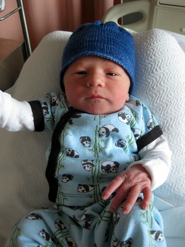 1 day old, wearing his knit hat.  Perfect fit!